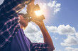Leinwandbild Motiv Close-up Of Asian man Hand Holding / looking / watching using Binoculars with copyspace, Technology Binoculars background concept