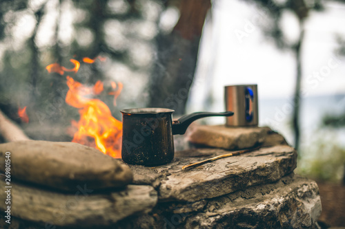 Making coffee in cezve on the fireplace when camping or hiking. coffee on campfire