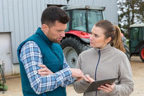 man and woman on farm looking at digital tablet Billede på lærred