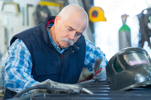 Photo portrait factory senior welder worker on manufacture workshop background