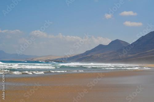 Poster Maroc Empty sandy ocean beach on a background of mountains. Fuerteventura Canary Islands, Spain