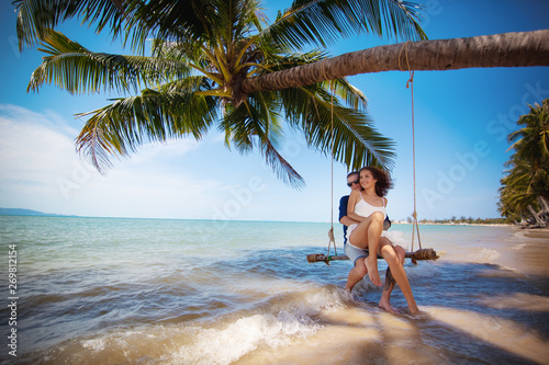 Couple on swing on tropical beach - 269812154