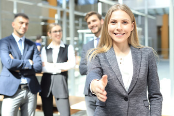 woman with an open hand ready for handshake in office.