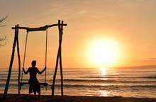 Silhouetted Female Tourist On Swing Watching Sunrise Over Sea, Gili Meno Island, Lombok, Indonesia