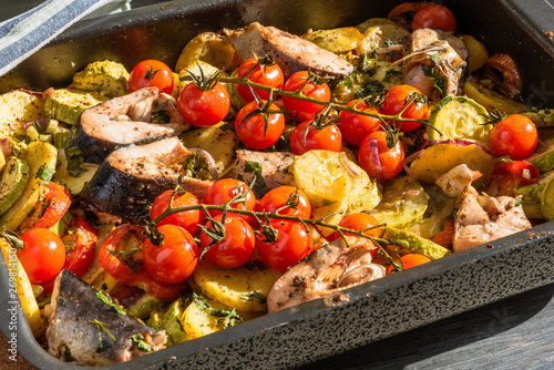 Valokuvatapetti Roast with vegetables and pieces of fish on a baking sheet - zucchini, cherry to