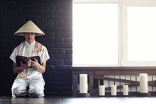 Asian Monk Reading An Old Book