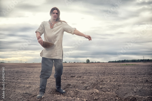A young peasant sows the field with grain Canvas Print