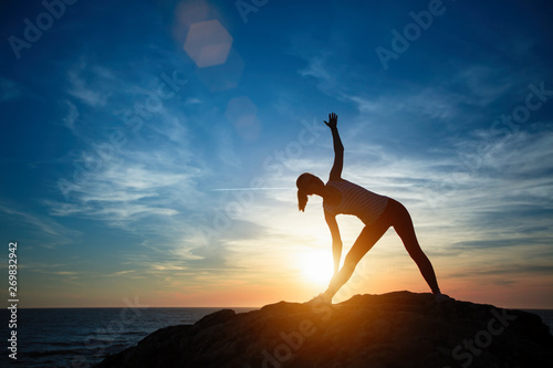 Foto  Silhouette of young woman doing exercises on the sea beach during sunset