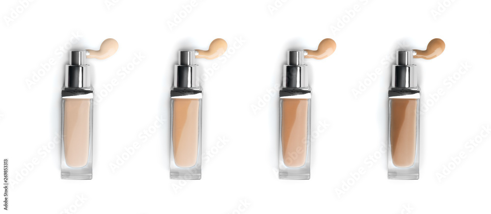 Fototapeta Foundation face makeup samples. Set of cosmetic liquid foundation or bb cream in bottles. Different colour smudge smear strokes isolated on white. Foundation colors palette