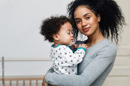 Fototapeta Young mom holding her sleepy baby boy. Beautiful mother with son in living room. obraz