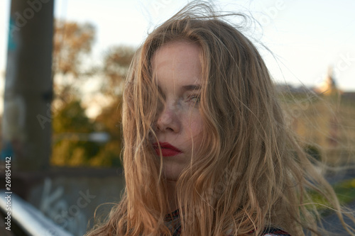 Fototapety, obrazy: Blonde in a plaid shirt in windy weather on railway tracks.