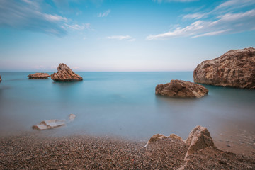 Fototapeta Morze Long exposure image of blue sky and sea with rocks in sunset scenery background. Sunset pebble sea beach among rocks and stones. Antalya. Turkey.