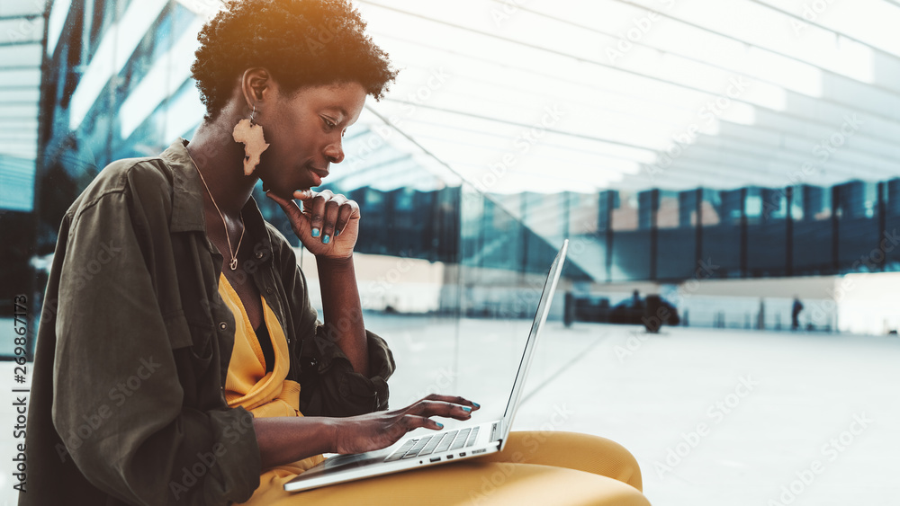 Fototapety, obrazy: A pensive black female entrepreneur with curly Afro hair with the laptop on the bench in an outdoor area of her office building; young charming African woman with the netbook is answering to e-mail