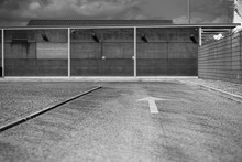 Black And White View Of An Asphalt Road With Selective Focus On A White Arrow Road Marking On It Following To Concrete Wall In A Defocused Background, Fencing On The Right, Shallow Depth Of Field