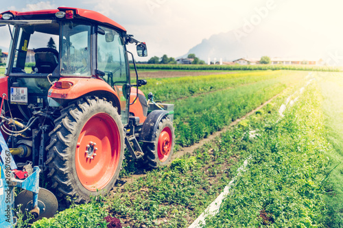 Photo Cut out of tractor cultivating field in spring, agriculture