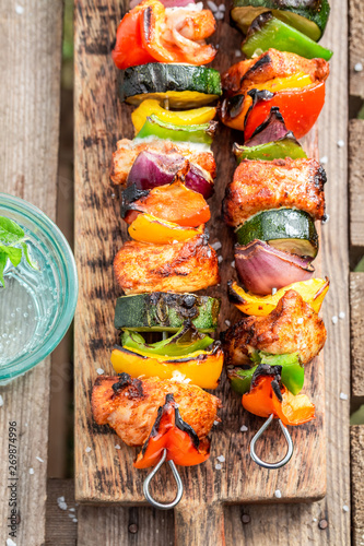 Spicy grilled skewers served with water in summer