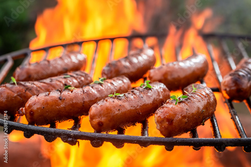 Carta da parati Closeup of hot sausage on grill with herbs and spices