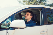 Successful Young Man Driving His New White Car Keeps Hand On The Steering Wheel Looking Ahead Happy Feeling Safe. Confident Businessman Smiling, Enjoying The Ride, Traveling.