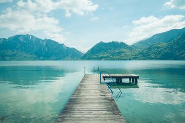 Drewniany pomost na spokojnym jeziorze w słoneczny dzień z błękitnym niebem. Na horyzoncie góry.