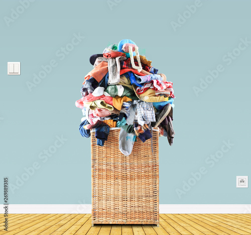 Photo Beige straw basket full of dirty Laundry