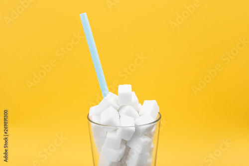 Fotomural  Glass of sugar cubes on a yellow background