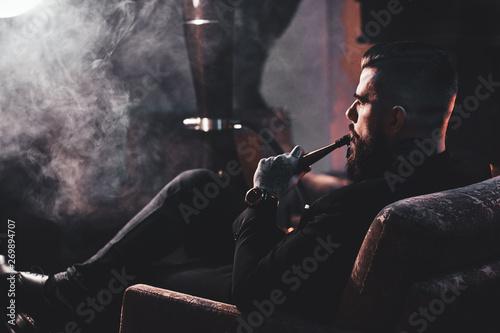 Fényképezés Groomed bearded man is relaxing on lounge near fireplace while smoking hookah