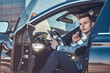 Young attractive businessman is sitting in his car at the parking while talking by mobile phone.
