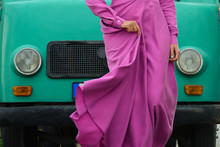 A Woman In A Magenta Fuchsia Silk Dress In Front Of A Mint Van On The Street.  Beautiful Violet Pink Dress With Swaying Form And Long Sleeves. Fashion Style.