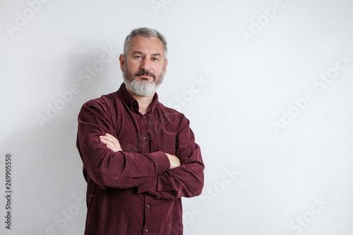 Half-length portrait of a serious gray-haired bearded man in a burgundy shirt on Billede på lærred