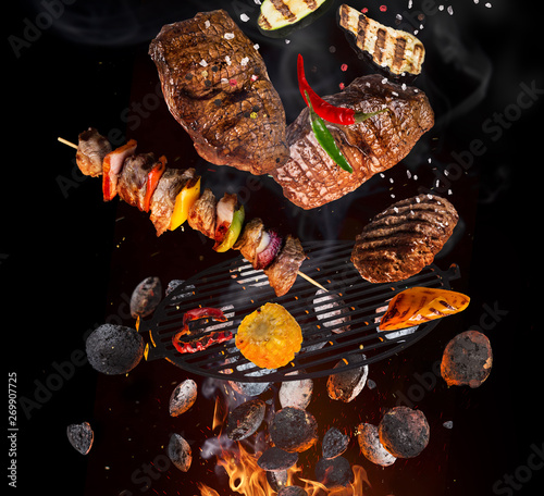 Fotografia Tasty beef steaks and skewers flying above cast iron grate with fire flames