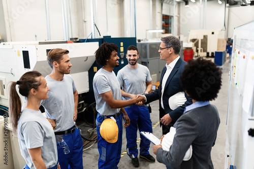 Happy corporate manager shaking hands with a worker while visiting a factory.