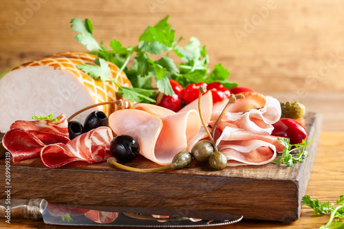 Assorti of sliced jamon, salami, ham with olives ,capers, pickles and stuffed red peppers