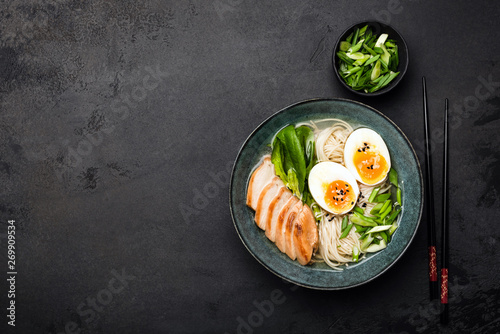 Photo  Asian ramen noodle soup with chicken on black concrete background