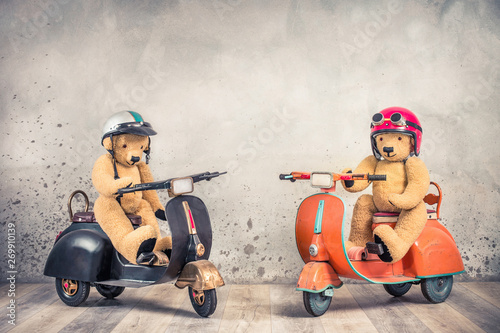 Scooter Retro Teddy Bear toys in helmets with goggles sitting on old children's pedal scooters from 60s front loft concrete wall background. Kids race competition concept. Vintage style filtered photo