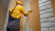 Worker painting wall with paint roller. Builder paints the wall in brown color. Building, renovation and people concept.