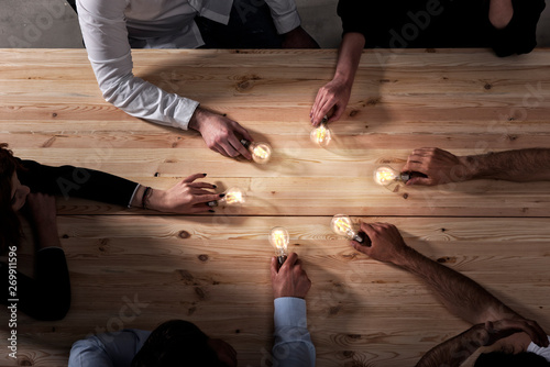 Cuadros en Lienzo Teamwork and brainstorming concept with businessmen that share an idea with a lamp