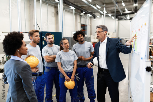 Photo  Mature businessman explaining new strategy plans to group of employees in a factory