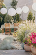 Flowers and plants on the wooden floor of elegant terrace with garden furniture set and white paper lamps, real photo