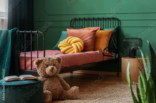 Fotografía Big, brown teddy bear and an open book on a green, velvet pouf in front of a metal frame bed in child's bedroom interior