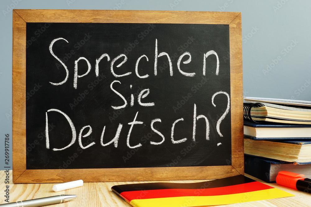 Fototapeta Sprechen Sie Deutsch written on a blackboard. Learn German concept.