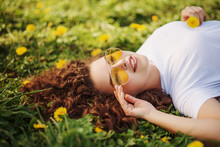 Outdoor Flat Lay, Top View Close Up Portrait Of Young Beautiful Happy Smiling Woman With Long Curly Hair, Wearing Stylish Yellow Sunglasses, Lying On The Meadow With Dandelions. Copy, Empty Space