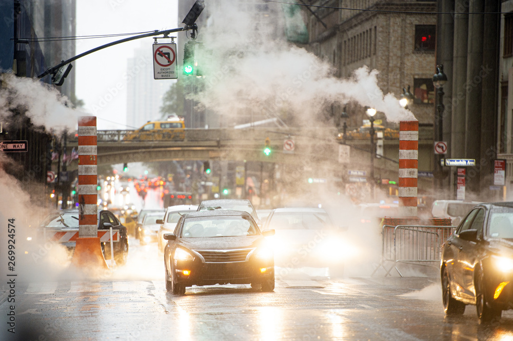 Fototapety, obrazy: Some cars are crossing the 42nd street in Manhattan while steam coming out from from the manholes. New York City, Usa. 42nd Street is a major crosstown street in Manhattan.