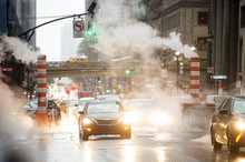 Some Cars Are Crossing The 42nd Street In Manhattan While Steam Coming Out From From The Manholes. New York City, Usa. 42nd Street Is A Major Crosstown Street In Manhattan.