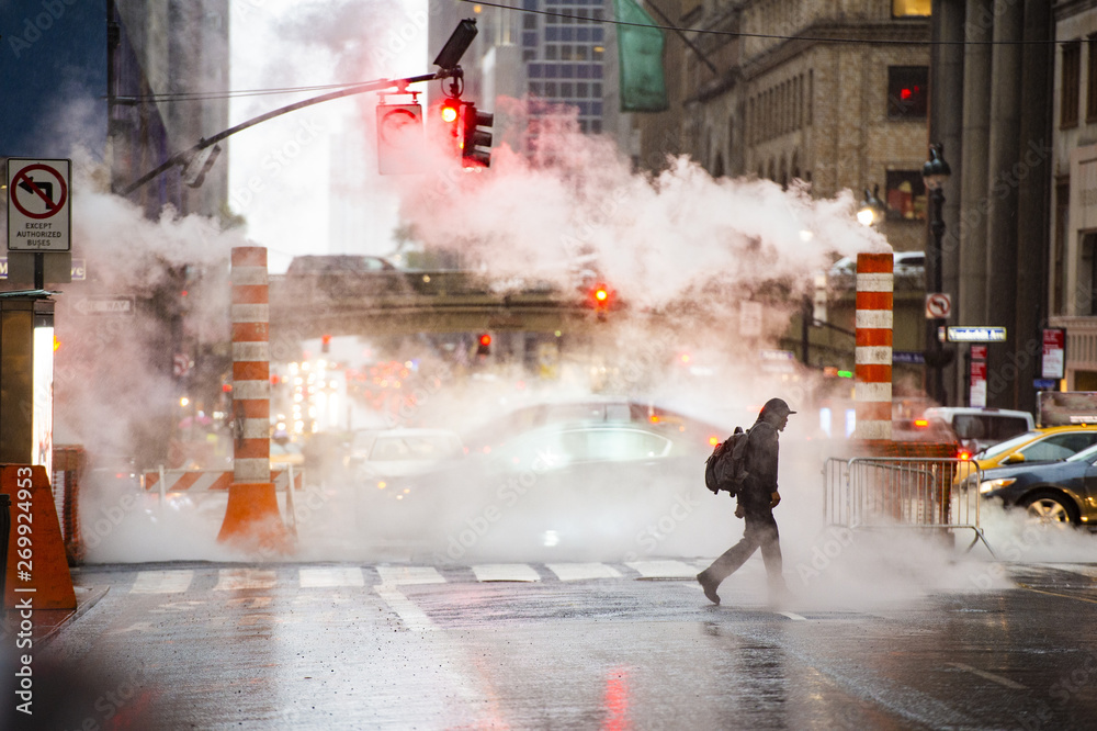 Fototapety, obrazy: A black male is crossing the 42nd street in Manhattan while steam coming out from from the manholes. 42nd Street is a major crosstown street in Manhattan, New York, USA.