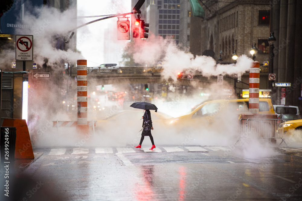 Fototapety, obrazy: A woman with an umbrella and red high heels shoes is crossing the 42nd street in Manhattan. Cars and steam coming out from from the manholes in the background. New York City, Usa.