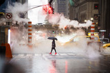 Fototapeta Nowy Jork - A woman with an umbrella and red high heels shoes is crossing the 42nd street in Manhattan. Cars and steam coming out from from the manholes in the background. New York City, Usa.