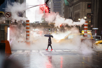 A woman with an umbrella and red high heels shoes is crossing the 42nd street in Manhattan. Cars and steam coming out from from the manholes in the background. New York City, Usa.