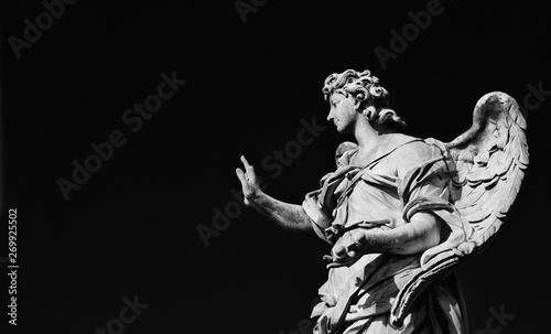 Angel statue holding the Nails of Jesus Cross. A 17th century baroque masterpiece at the top of Sant'Angelo Bridge in the center of Rome (Black and White with copy space) - 269925502