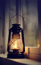 An Old Kerosene Lamp Stands On A White Windowsill