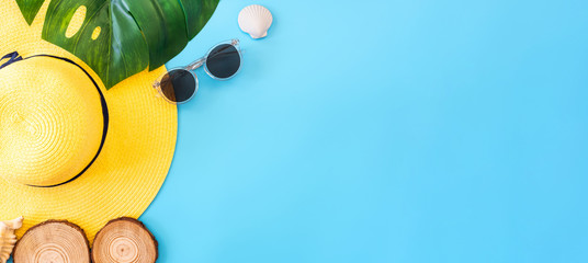 summer blue banner with yellow hat ,sunglasses,seashell and monstera leaf on blue background top view.